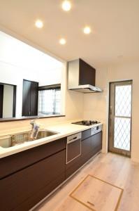 キッチンの扉も茶色の板目で統一。取っ手がないだけですっきりします。